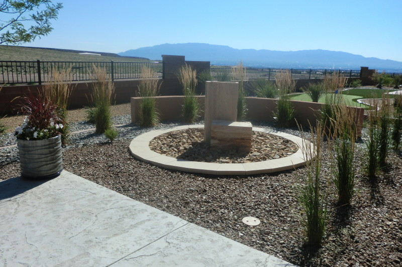 Golf Course Landscaping with rock sculpture in center of flagstone circle and native new mexican plants