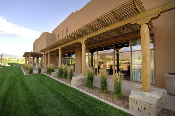 Southwestern designed building with grass surrounded by xeriscape design