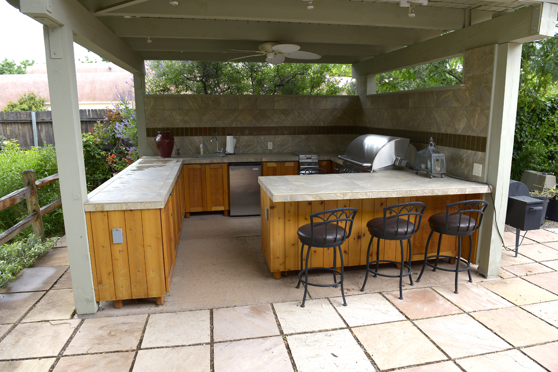 Residential backyard with covered outside kitchen with bbq grill, mini fridge and bar area