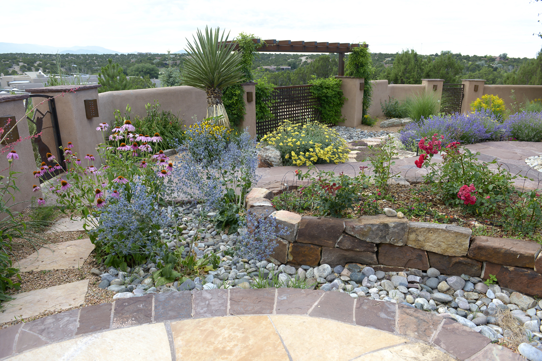 backyard with xeriscape flagstone patio and walkways with flowers and flowering bushes throughout