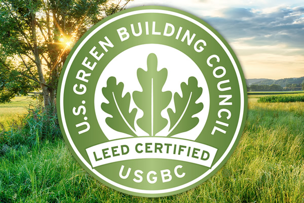 U.S. Green Building Council LEED Certified USGB Logo in front of field of grass and trees