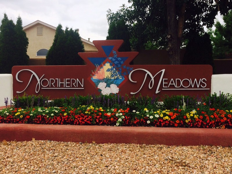 Northern Meadows sign surrounded by flowers and xeriscape rock ground cover